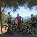 Three people on bikes in the mountains